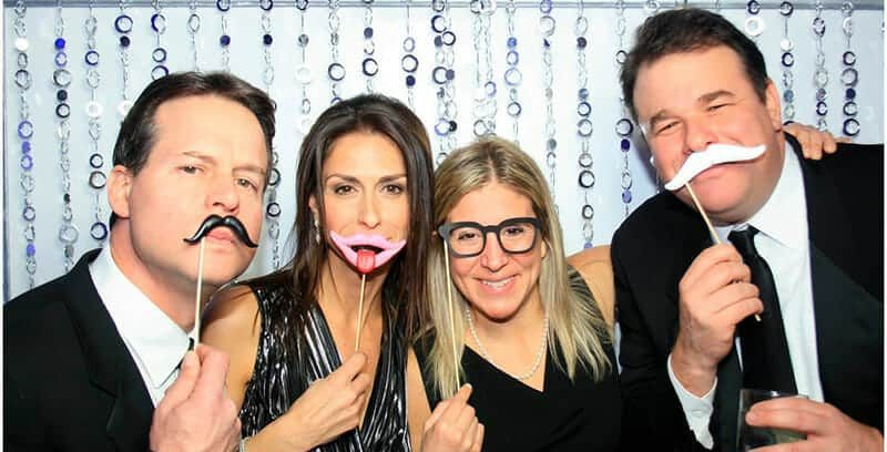 picture of two couples in photo booth with mustache props