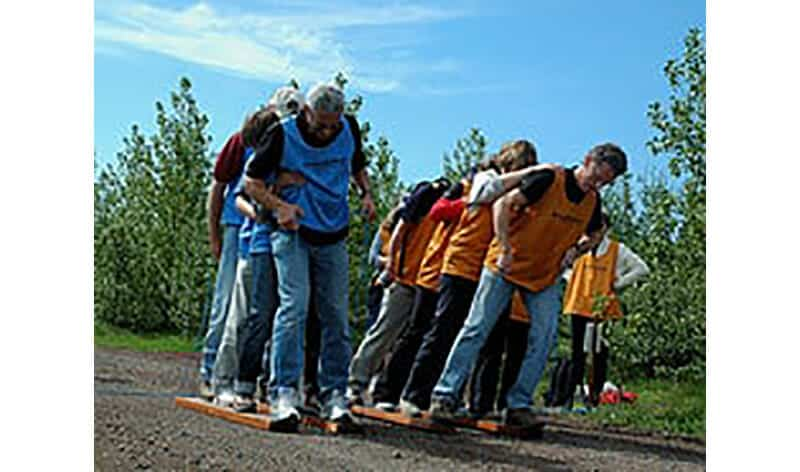 Team building activity of groups of four people walking together on set of boards